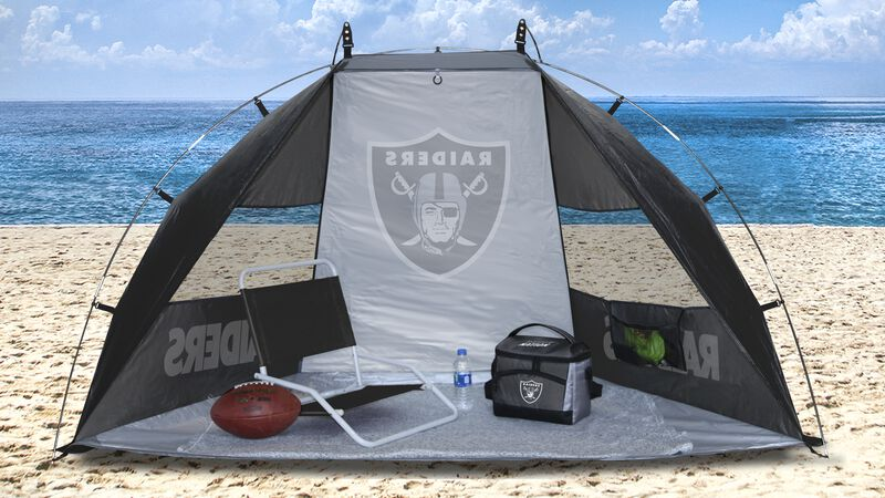 A Las Vegas Raiders sideline sun shelter set up on a beach with a chair, football, cooler and water bottle - SKU: 00961072111
