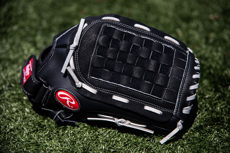A black RSB Basket web glove lying in the grass on a field - SKU: RSB140GB