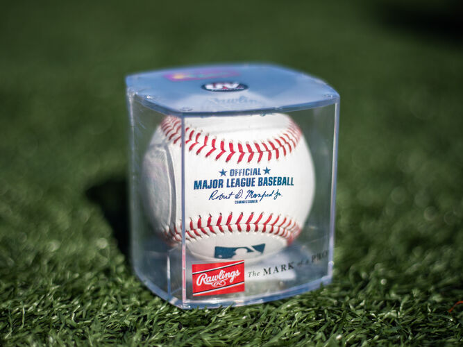 Official Major League baseball in a display cube sitting on a field - SKU: ROMLB-R