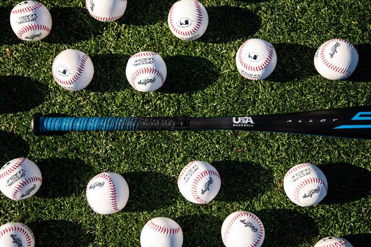 Baseballs on the ground around the handle of a USA Baseball 5150 youth bat - SKU: US15