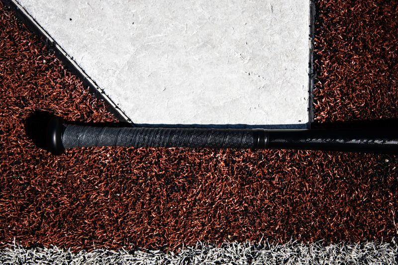 Grey/black grip tape of a Rawlings Velo ACP BBCOR baseball bat lying next to home plate - SKU: BBZV3