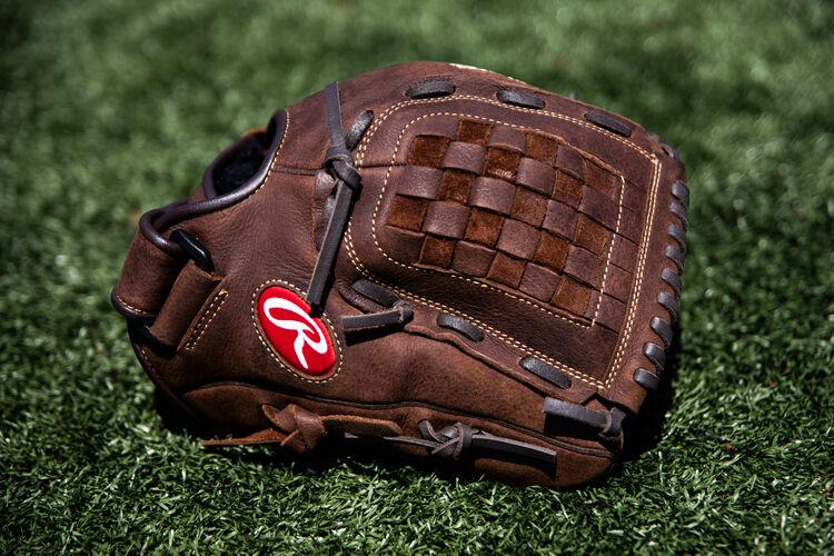 A Player Preferred 12-inch Basket web glove lying on a field - SKU: P120BFL