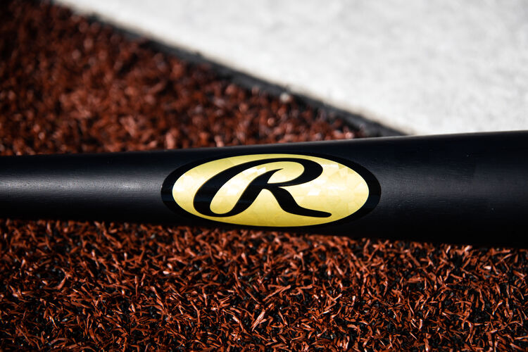 Gold foil Rawlings Oval-R on a black Khris Davis bat lying next to home plate - SKU: KD2PL