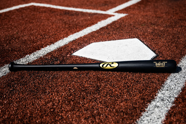 A black Khris Davis Pro Label bat lying next to home plate - SKU: KD2PL
