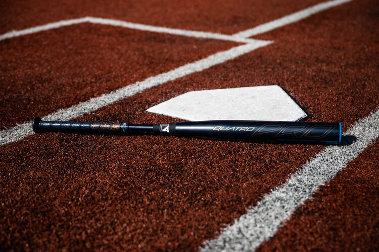 A Rawlings Quatro Pro End Load fastpitch bat lying next to home plate on a field - SKU: FPPE10