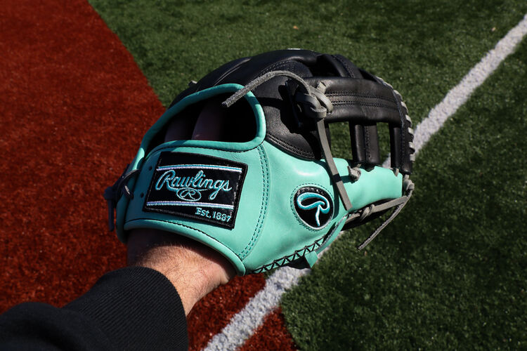 A HOH ColorSync 5.0 11.5-Inch infield glove on a players hand with a field in the background - SKU: PRONP4-20BOM