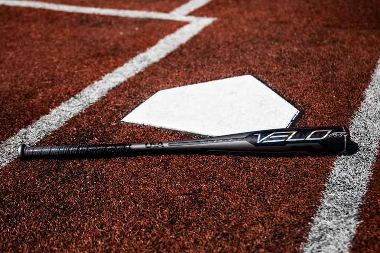 A grey Rawlings 2020 Velo ACP USA bat lying on a field next to home plate - SKU: USZV10