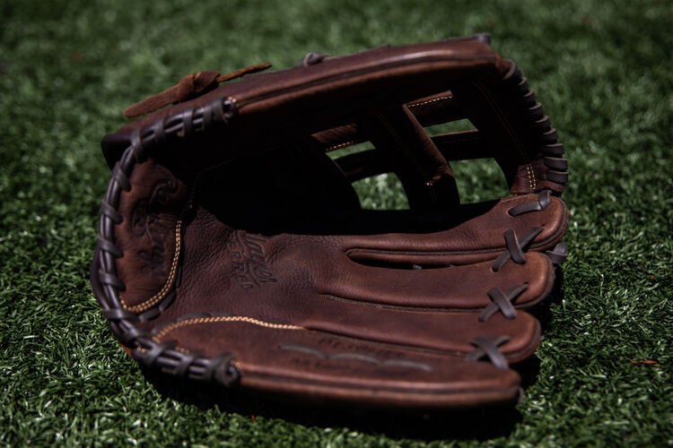 Brown palm of a Rawlings Player Preferred glove lying on a field - SKU: P130HFL
