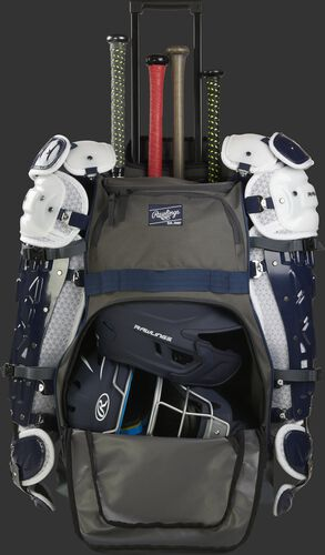 A grey/navy R1801 wheeled equipment backpack with leg guards secured and a batting and catcher helmet in the main compartment