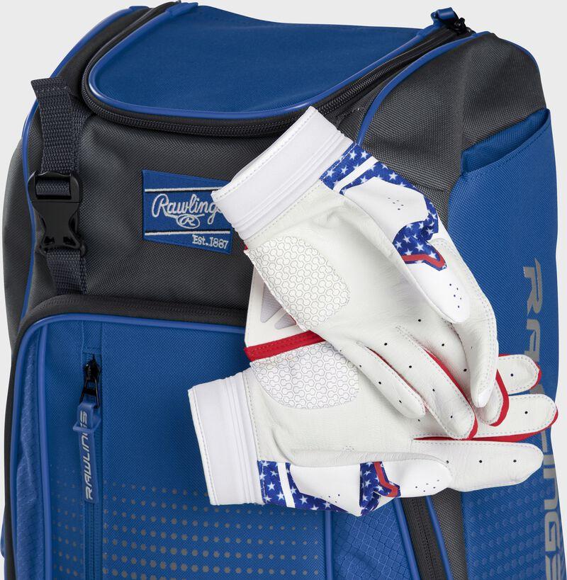 Two batting gloves hanging on the front Velcro strap of a Franchise baseball backpack - SKU: FRANBP-R