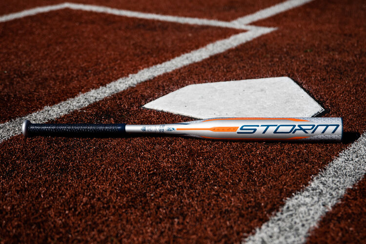 A silver Rawlings 2020 Storm bat lying on a field next to home plate - SKU: FPZS13