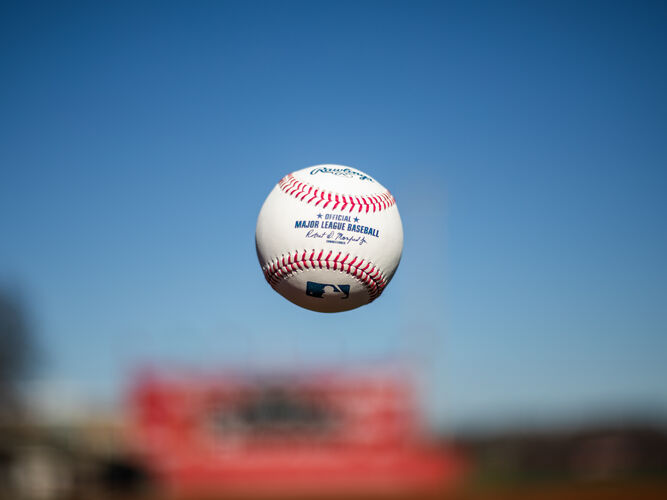 A Rawlings Major League baseball tossed in the air with the sky in the background - SKU: ROMLB