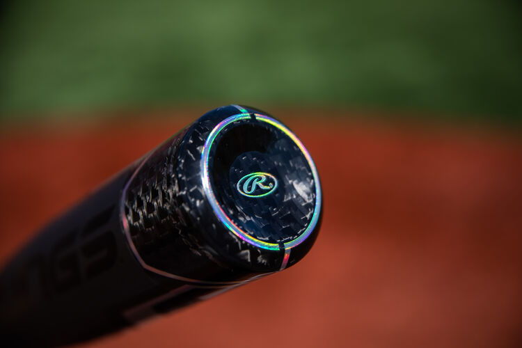 Carbon fiber end cap on a USA -10 Velo ACP bat with a field in the background - SKU: USZV10