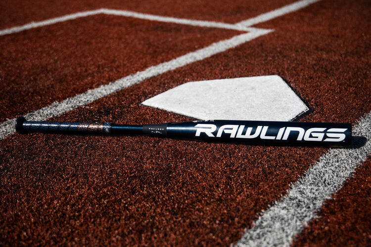 A Rawlings fastpitch Quatro Pro bat lying on a field next to home plate - SKU: FPZP9