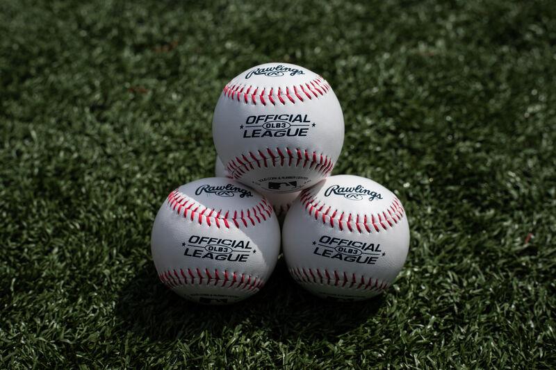 Three Rawlings baseball lying together in a triangle on a field - SKU: OLB3