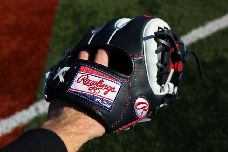 A Rawlings Heart of the Hide ColorSync 5.0 infield glove on a players hand with a field in the background - SKU: PRO314-2NW