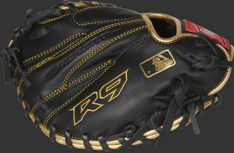 Back of a black R9 training catcher's mitt with gold stitching and MLB logo on the pinkie - SKU: R9TRCM