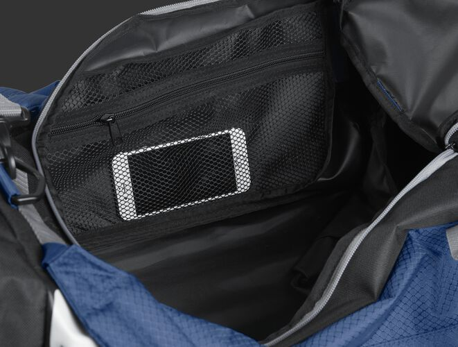 A phone inside the mesh accessory pocket inside the main compartment of a navy R601 Hybrid bag