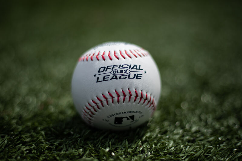An Official League baseball lying on a field with the MLB logo showing on the bottom - SKU: OLB3