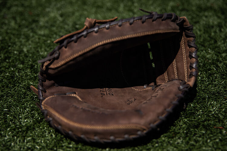 Brown palm of a Player Preferred recreational mitt lying on a field - SKU: PCM30