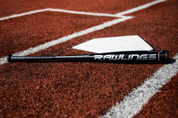A Rawlings Velo ACP bat lying next to home plate on a field - SKU: BBZV3