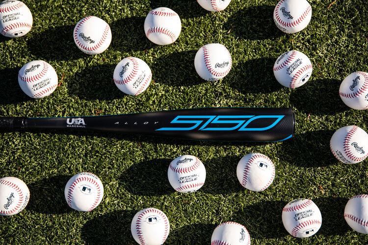 A Rawlings USA 5150 bat on a field with baseballs around it - SKU: US15