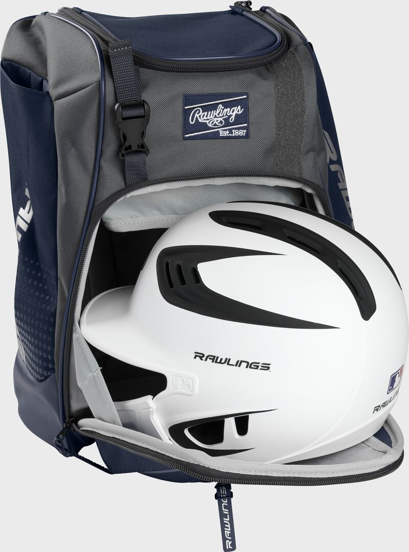 A white/black helmet in the main compartment of a navy Rawlings Franchise backpack - SKU: FRANBP-N
