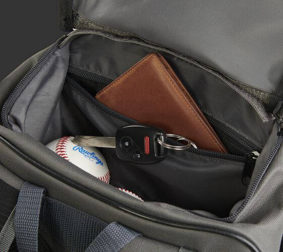 Personal items in the top valet tray pocket of a gray R701 universal training backpack