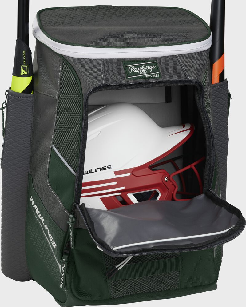 A dark green Impulse baseball backpack with a helmet in the main compartment - SKU: IMPLSE-DG