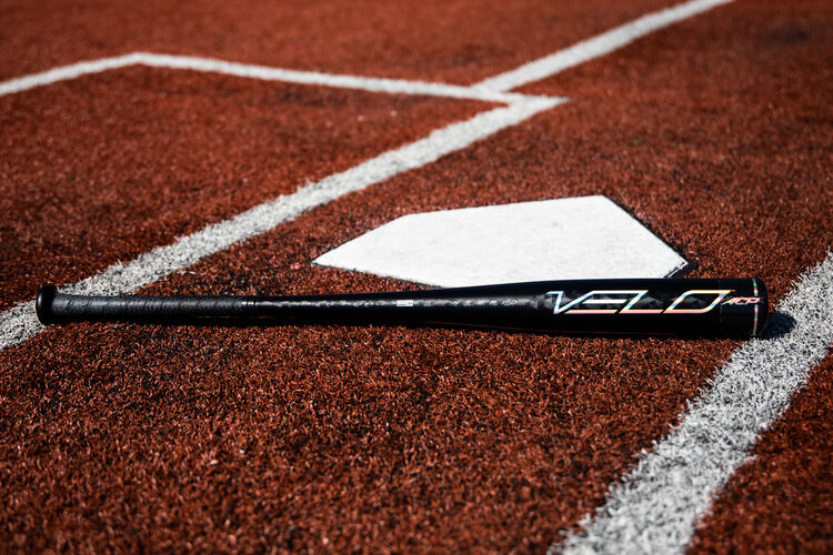 A black/silver Rawlings Velo ACP BBCOR bat on a field next to home plate - SKU: BBZV3