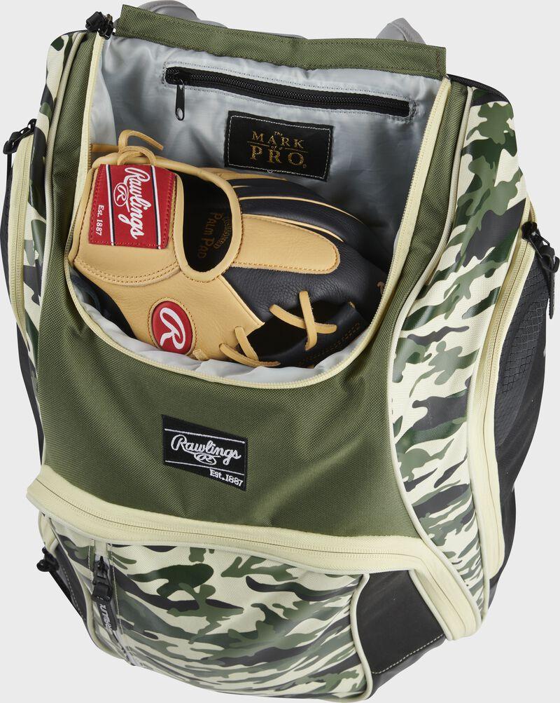 A glove in the dedicated glove storage pocket of a Rawlings Legion equipment backpack - SKU: LEGION-CAMO