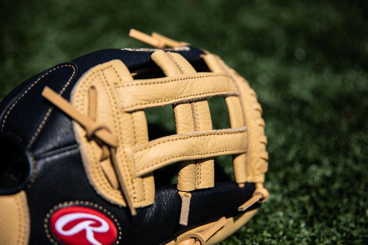 A camel H-web on a Prodigy outfield glove lying on a field - SKU: P120CBH