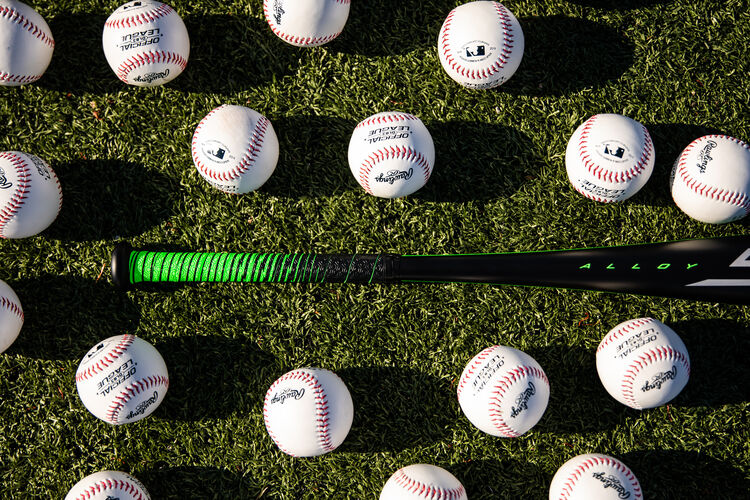 Handle of a 2021 Rawlings 5150 bat laying on a field surrounded by baseballs - SKU: UT1510