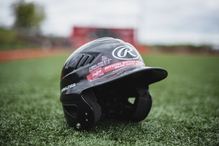A black Coolflo batting helmet sitting on a field - SKU: RCFH
