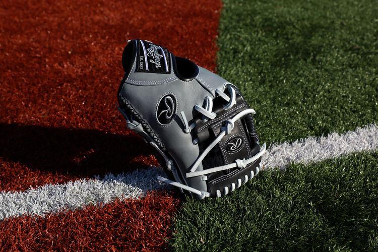 A black/gray HOH ColorSync 5.0 Hyper Shell I-web glove standing on it's finger tips on a field - SKU: PRO205W-2BWG