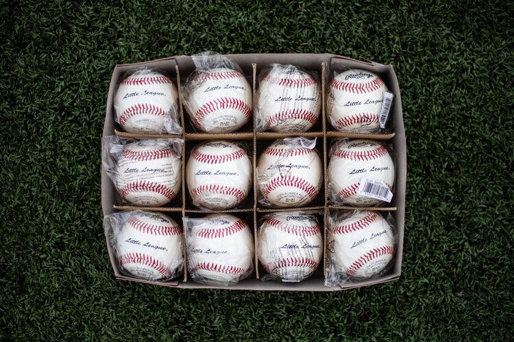 A box of a dozen Rawlings Little League balls lying on a field - SKU: RLLB1