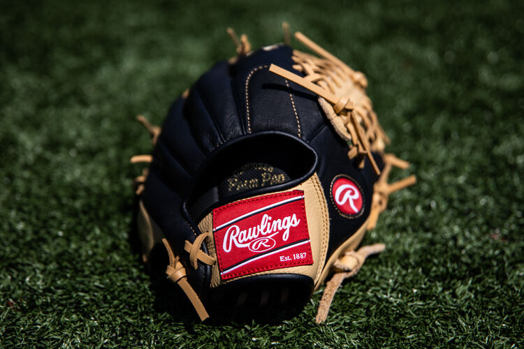Rawlings patch on a Rawlings youth Prodigy glove lying on a field - SKU: P115CBMT