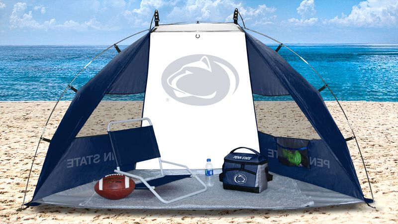 A Penn State Nittany Lions sun shelter set up on a beach with a cooler, football, chair and water bottle - SKU: 00973050111