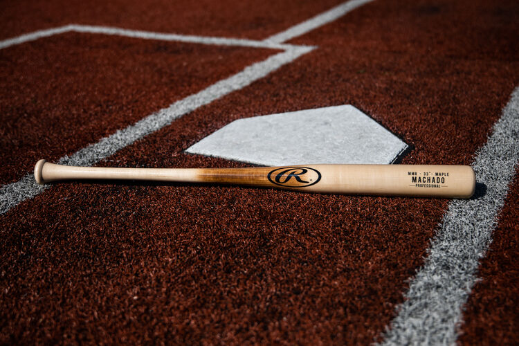 A Rawlings Manny Machado Pro Label bat lying next to home plate - SKU: MM8PL