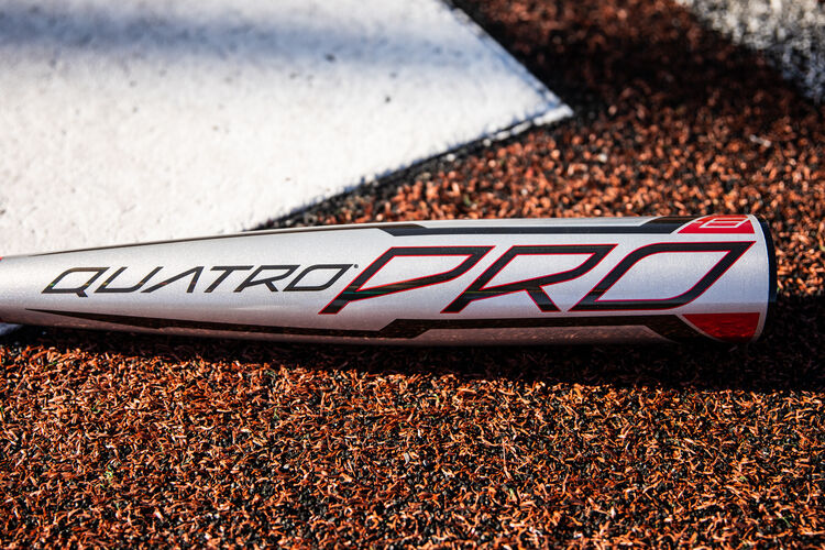 A black Quatro Pro logo on the gray barrel of a USA Quatro Pro bat next to home plate - SKU: US1Q8