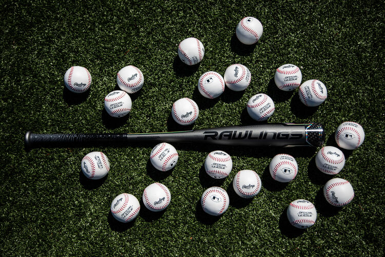 A Rawlings USA Velo ACP bat lying on a field surrounded by baseballs - SKU: USZV10