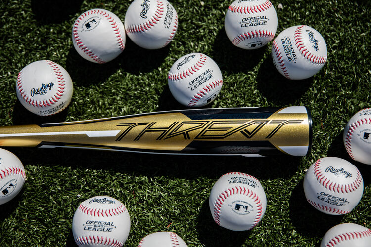 Gold barrel of a -12 Threat USA bat lying on a field with baseballs - SKU: USZT12