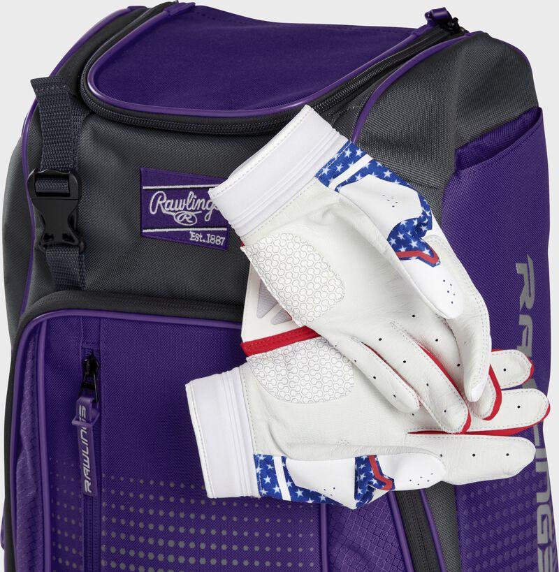 Two batting gloves hanging on the front Velcro strap of a Franchise baseball backpack - SKU: FRANBP-PU