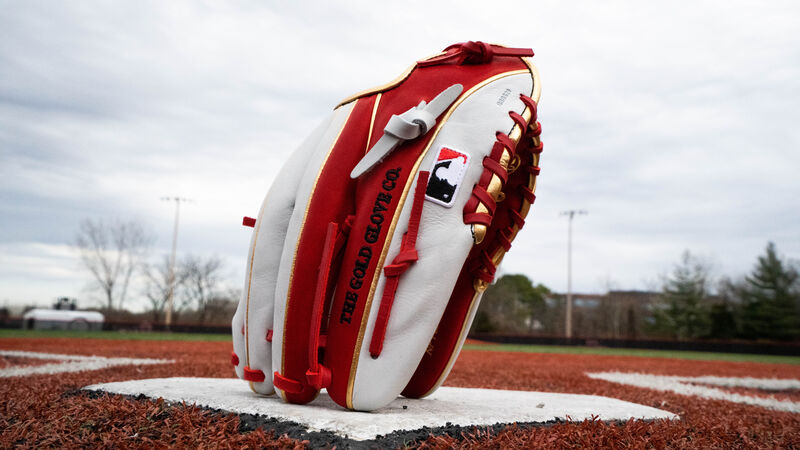A scarlet/white Rawlings HOH exclusive infield glove standing on its finger tips on home plate - SKU: PRONP2-8SW