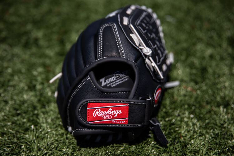Rawlings patch on the wrist strap of a Rawlings Softball series glove lying on a field - SKU: RSB120GB