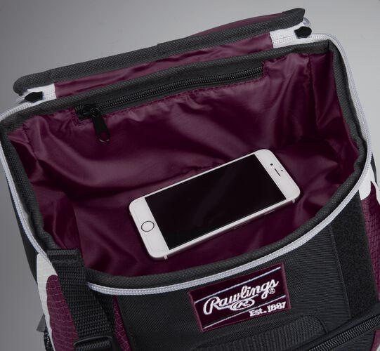Top accessory pocket of a black/maroon R500 equipment backpack holding a phone