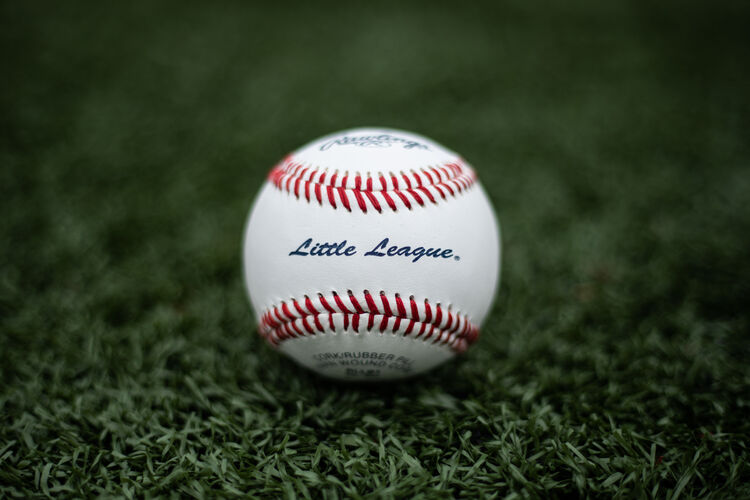 A Rawlings Little League baseball lying in the grass on a field - SKU: RLLB1