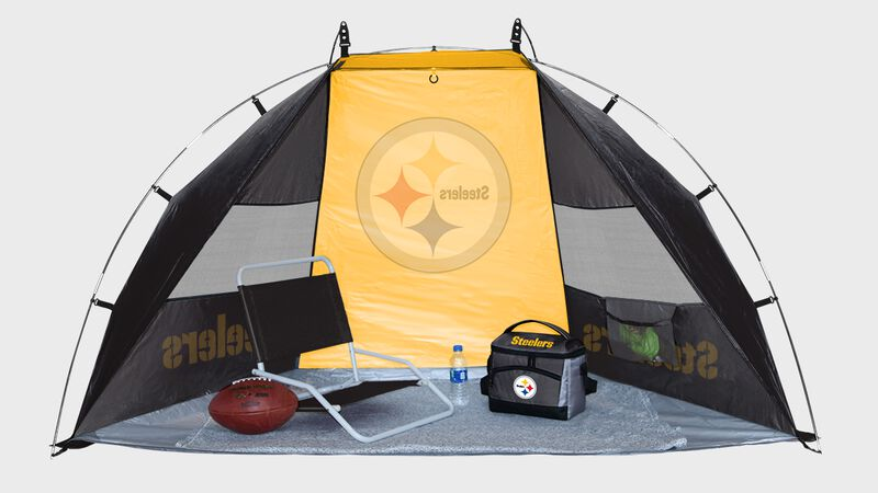 Inside of a Pittsburgh Steelers shelter tent with a chair cooler and ball