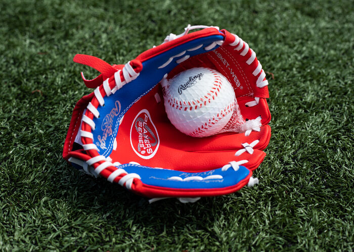 A baseball in the palm of a Rawlings Player Series youth glove lying on a field - SKU: PL91SR