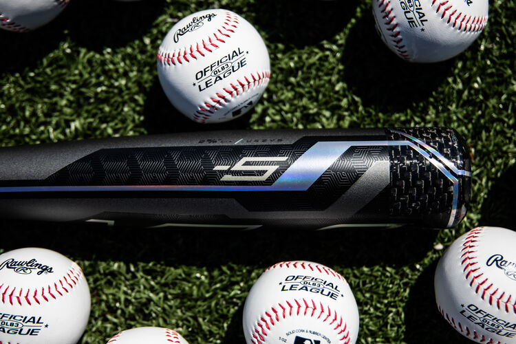 Barrel of a Velo ACP USA bat lying on a field with baseballs - SKU: USZV5
